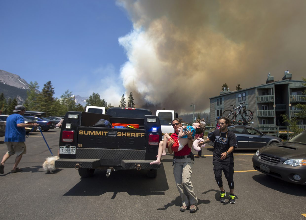 A Wildernest family, including a 9-year-old with cerebral palsy, are assisted by the Summit County Sheriff's Office's Erin Sirek. Deputies gave the family a ride out of the neighborhood, which was evacuated on Tuesday as a wildfire threatened the area.