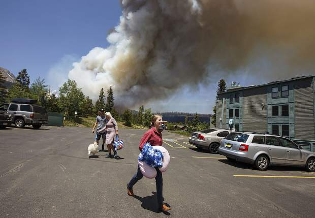 Residents evacuate their homes as a wildland fire approaches in the Wildernest neighborhood Tuesday, June 12, near Silverthorne.