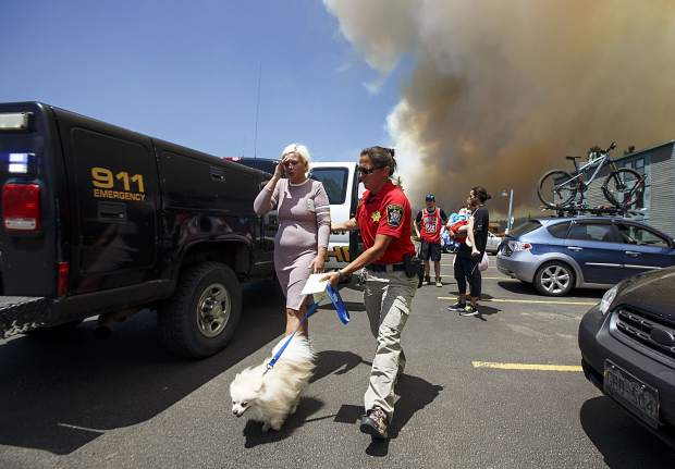 Lana Eltsova and her dog Pompon evacuate their homes with help from Summit County Sheriff Department's Erin Sirek as the wildland fire approaches in the Wildernest neighborhood Tuesday, June 12, near Silverthorne.
