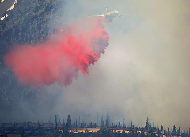 A fire retardant aircraft flies over the wildland fire in the Wildernest neighborhood Tuesday, June 12, near Silverthorne.