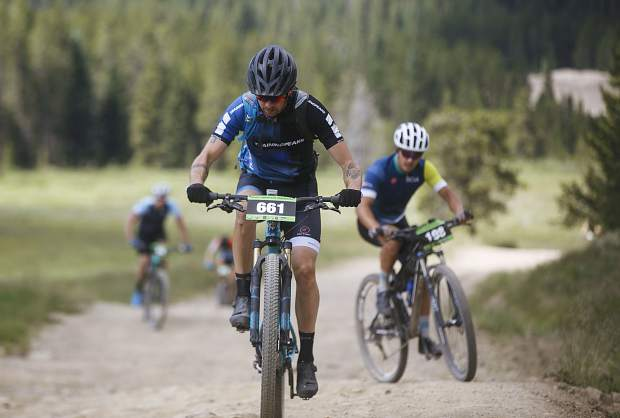 Mountain bikers participating in the Breckenridge 100 climbs in the North Fork valley of the Swan River Saturday, July 14, near Keystone.