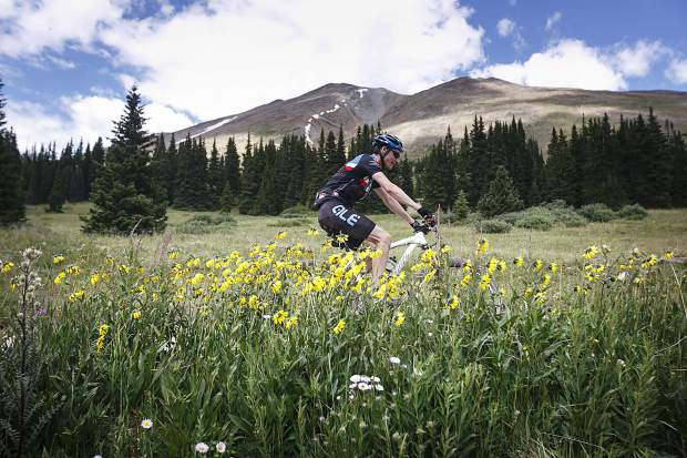 A mountain biker participating in the Breckenridge 100 climbs past wildflowers on Boreas Pass Road Saturday, July 14, in Breckenridge.