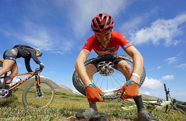 Todd Gearhart fixes a flat tire as racers ride by on the Wheeler Trail during Stage 5 of the Breck Epic multi-day mountain bike race in August 2016. Ironman has approached the town of Breckenridge and race founder Mike McCormack about taking over the annual event and branding it as the premier mountain bike event in all of North America. The town council is set to make a decision at Tuesday's work session.