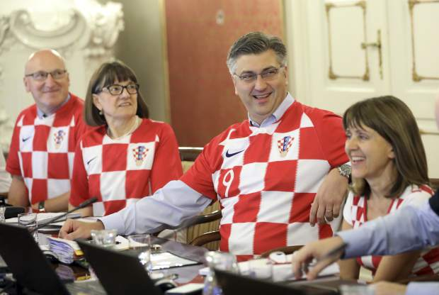 Croatia's Prime Minister Andrej Plenkovic, center, sits between ministers wearing Croatian national soccer team jerseys during a government session in Zagreb, Croatia on Thursday, July 12, a day after Croatia qualified to the finals at the soccer World Cup.
