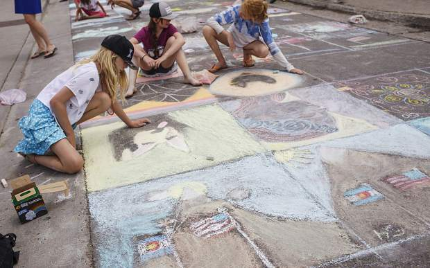 Breckenridge residents Molly Gaertner, left to right, Haven Leinweber, and Olivia Feest use chalk to create art on the street on Wednesday, July 4, in the Arts District of Breckenridge.