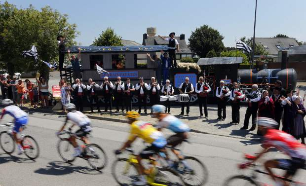 Musicians perform on the side of the road as the pack with Belgium's Greg van Avermaet, wearing the overall leader's yellow jersey, center, rides during the sixth stage of the Tour de France cycling race over 181 kilometers (112.5 miles) with start in Brest and finish in Mur-de-Bretagne Guerledan, France, Thursday, July 12, 2018.