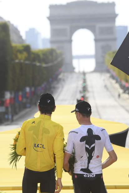 Tour de France winner, Britain's Geraint Thomas, wears the overall leader's yellow jersey, and third place-finisher Chris Froome, also of Britain, celebrate on the podium after the twenty-first stage of the Tour de France cycling race, which included over 116 kilometers (72.1 miles) with a start in Houilles and finish on Champs-Elysees avenue in Paris, France, on Sunday.
