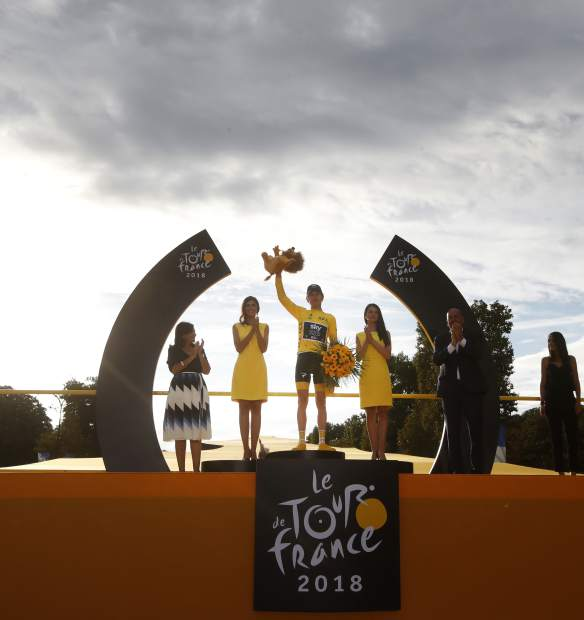 Tour de France winner, Britain's Geraint Thomas, wears the overall leader's yellow jersey and celebrates on the podium after the twenty-first stage of the Tour de France cycling race, which included over 116 kilometers (72.1 miles) with a start in Houilles and finish on Champs-Elysees avenue in Paris, France, on Sunday.