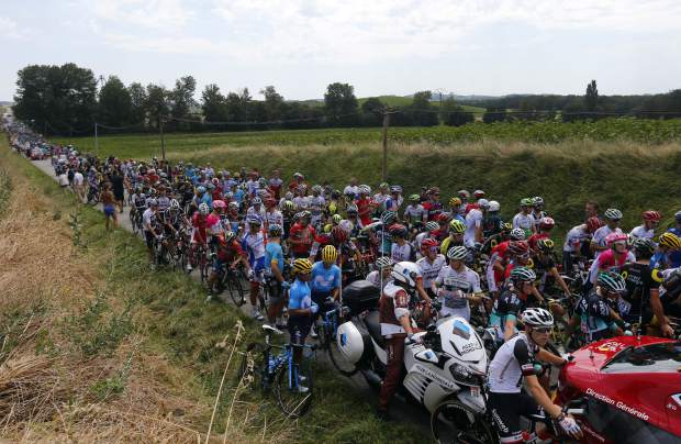 Riders wait on the road after a farmer's protest interrupted the sixteenth stage of the Tour de France cycling race over 218 kilometers (135.5 miles) with start in Carcassonne and finish in Bagneres-de-Luchon, France, on Tuesday, July 24.