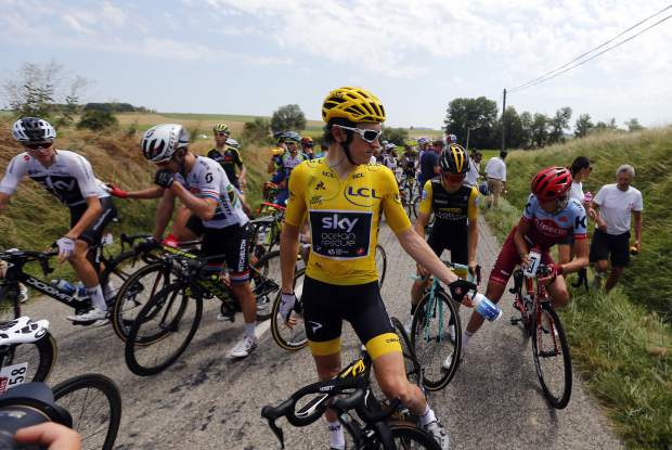Riders with Britain's Geraint Thomas, wearing the overall leader's yellow jersey, wait on the road after a farmer's protest interrupted the sixteenth stage of the Tour de France cycling race over 218 kilometers (135.5 miles) with start in Carcassonne and finish in Bagneres-de-Luchon, France, on Tuesday, July 24.