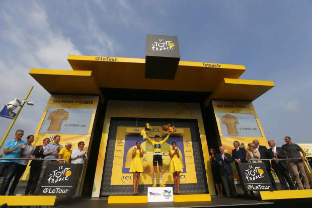 Britain's Geraint Thomas, wearing the overall leader's yellow jersey, celebrates on the podium after the eighteenth stage of the Tour de France cycling race over 171 kilometers (106.3 miles) with start in Trie-sur-Baise and finish in Pau, France on Thursday.