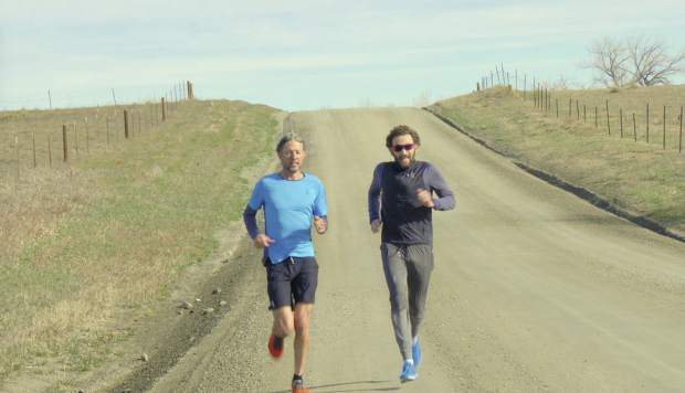 This March 2018 image provided by On shows Olivier Bernhard, left, running with Tim Don in Boulder. A few days before the 2017 Ironman world championships in Hawaii, British-born triathlete Don was out on a training ride when he got hit by a truck. For three months, the 40-year-old world-record holder wore a halo to stabilize his broken neck. The memory of what he wanted to accomplish that week as one of the favorites are as vivid as ever. Nicknamed
