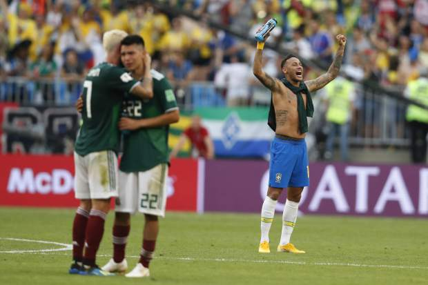 Brazil's Neymar celebrates as Mexico's Miguel Layun and teammates Hirving Lozano embrace at the end of their round of 16 match at the 2018 soccer World Cup in the Samara Arena, in Samara, Russia on Monday, July 2. Brazil won 2-0.