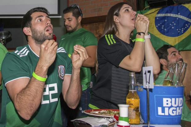 Mexico fans Marcel Shorago and Christina Muniz react as they watch a FIFA World Cup Round of 16 knockout match between Brazil and Mexico at B-Vares in Miami, Fla., on Monday, July 2. Brazil defeated Mexico 2-0.