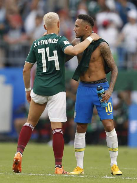 Mexico's Javier Hernandez (14) embraces Brazil's Neymar after their Round of 16 match at the 2018 soccer World Cup in the Samara Arena, in Samara, Russia on Monday, July 2. Brazil won 2-0.