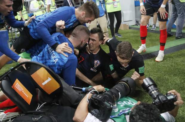 Croatia's Mario Mandzukic, sits on the ground after he fell over a photographer when celebrating his side's second goal during the semifinal match between Croatia and England at the 2018 soccer World Cup in the Luzhniki Stadium in Moscow, Russia on Wednesday, July 11.