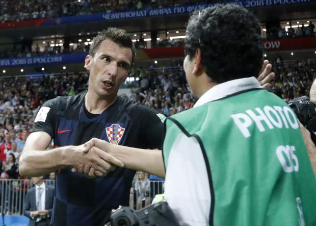 Croatia's Mario Mandzukic apologizes to a photographer he fell over when celebrating his side's second goal during the semifinal match between Croatia and England at the 2018 soccer World Cup in the Luzhniki Stadium in Moscow, Russia on Wednesday, July 11.