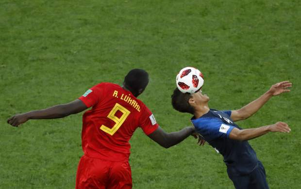 Belgium's Romelu Lukaku, left, jumps for the ball with France's Raphael Varane during the semifinal match between France and Belgium at the 2018 soccer World Cup in the St. Petersburg Stadium in St. Petersburg, Russia on Tuesday, July 10.