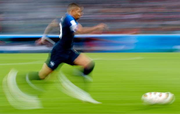 In this photo taken with slow-shutter speed, France's Kylian Mbappe runs with the ball during the semifinal match between France and Belgium at the 2018 soccer World Cup in the St. Petersburg Stadium, in St. Petersburg, Russia on Tuesday, July 10.