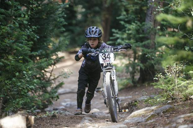 Junior boys 10 & under competitor Jack Shingles of Wilderness Sports Jr. pushes his mountain bike uphill during the fourth Summit Mountain Challenge mountain bike event of the summer series, the Pennsylvania Gulch Grind, on Wednesday, July 18, in Breckenridge.