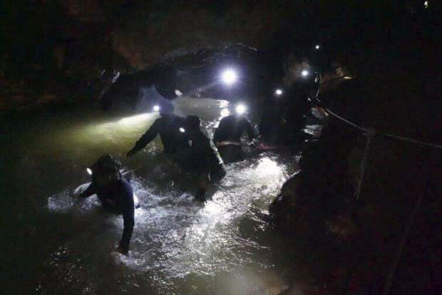In this handout photo released by the Tham Luang Rescue Operation Center, Thai rescue teams walk inside the cave complex where 12 boys and their soccer coach went missing, in Mae Sai, Chiang Rai province, in northern Thailand, Monday, July 2, 2018. Rescue divers are advancing in the main passageway inside the flooded cave in northern Thailand where the boys and their coach have been missing more than a week.