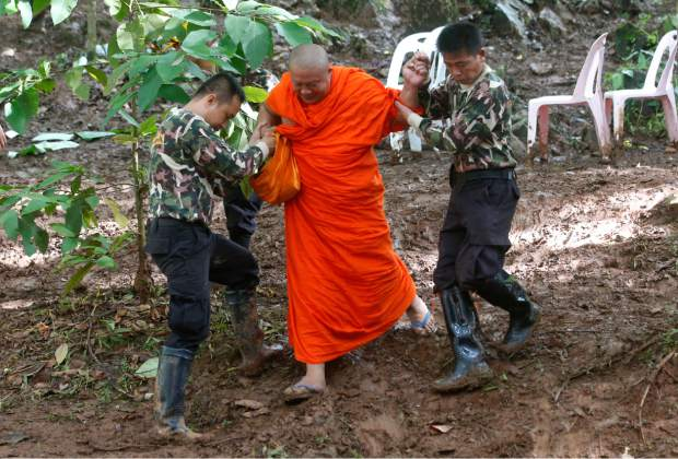 A Buddhist monk, helped by Thai rescues, walks after praying near a cave complex where 12 boys and their soccer coach went missing, in Mae Sai, Chiang Rai province, in northern Thailand, Sunday, July 1, 2018. The frantic effort to locate them in the cave for a week picked up pace as a break in the rain eased flooding in the system of caverns and more experts from around the world joined the anxious rescue mission.