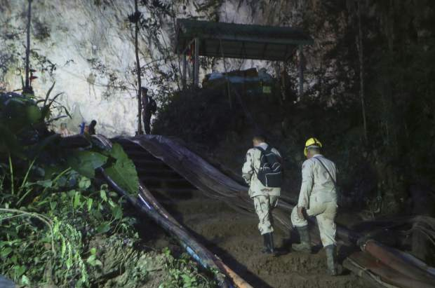 Rescuers make their way up at the entrance to a cave complex where 12 boys and their soccer coach went missing, in Mae Sai, Chiang Rai province, in northern Thailand, Monday, July 2, 2018. Rescue divers are advancing in the main passageway inside the flooded cave in northern Thailand where the boys and their coach have been missing more than a week.