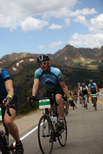 A rider signals to the camera during Saturday's Triple Bypass event, an annual 120-mile bike ride for more than 4,000 cyclists up and over several mountain passes east to west, from Evergreen to Avon. The event returned this year after wildfires cancelled the tour in 2017.