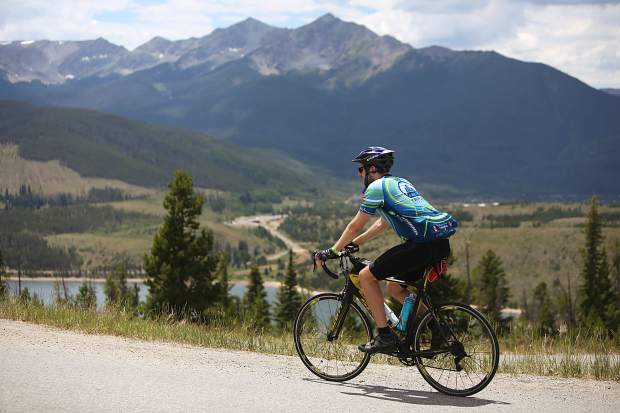 With the Ten Mile Range's iconic Peaks 1 and 2 in view in the background behind Lake Dillon, a cyclist ascends Swan Mountain Road during Saturday's Triple Bypass event. The annual 120-mile bike ride for more than 4,000 cyclists returned this year after wildfires, including one on Peak 2, cancelled the tour in 2017, riders pedaling up and over several mountain passes east to west, from Evergreen to Avon.