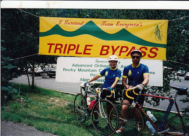 Triple Bypass riders pose for a photo in front of a sign handmade by Team Evergreen during a previous installment of the 120-mile ride from Evergreen to Avon.