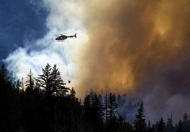 A helicopter transports water to contain the Weston Pass FIre Monday, July 2, near Fairplay.
