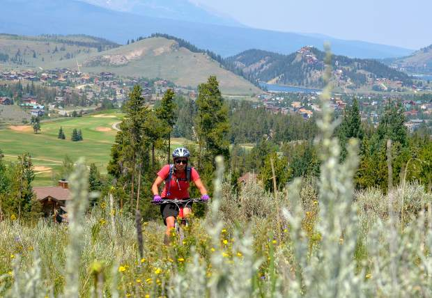 Summit local Sara Skinner rides past sage and wildflowers on the Aqueduct trail in Keystone, CO.