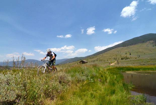 A cyclist passes by the beaver pond at Keystone Ranch on the Soda Creek Trail in Keystone, CO.