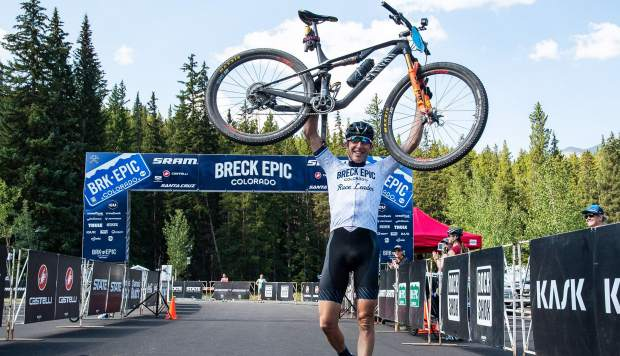 Jeremiah Bishop holds his mountain bike over his head after completing the 2018 Breck Epic multi-stage mountain bike race in first-place overall, his fourth career win at the event.