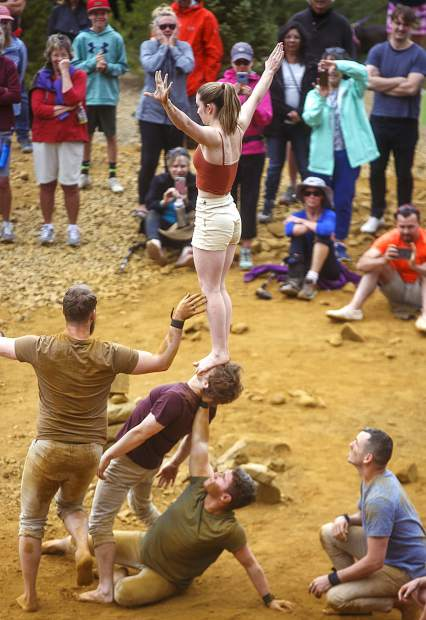 Acrobats of the Gravity & Other Myths Ashleigh Pearce stands on the face of Joshua Strachan during the performance in front of crowds along the Wellington Trail Thursday, Aug. 16, in Breckenridge.
