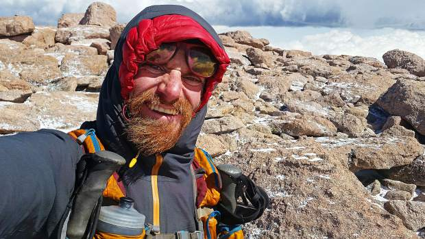 Justin Simoni, 37, of Boulder musters a smile near the 14,259-foot summit of Long's Peak, which was the final mountain he scaled during his 60-plus day summer 2017 self-supported bike-and-hike journey of the105 highest mountains in Colorado. On Wednesday, he spoke about the odyssey to local Summit County folk at Wilderness Sports in Dillon.