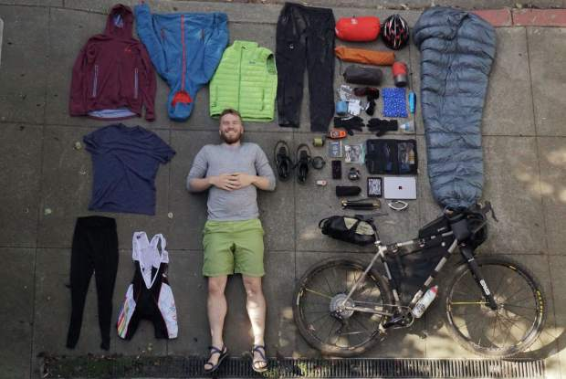 Devon Proctor of San Francisco poses for a photo whiling laying down with all of his bikepacking gear sprawled out around him. Proctor and Caitlin Hewitt stopped in Frisco last week during their 19,000-mile, year-long bikepacking journey from Prudhoe Bay, Alaska down to Ushuaia, Argentina.