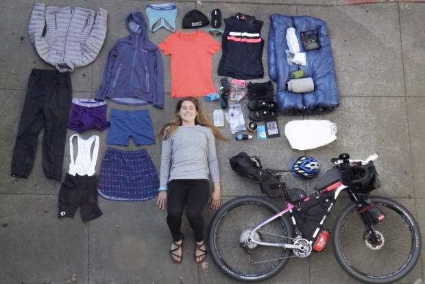 Caitlin Hewitt of San Francisco poses for a photo whiling laying down with all of her bikepacking gear sprawled out around her. Hewitt and Devon Proctor stopped in Frisco last week during their 19,000-mile, year-long bikepacking journey from Prudhoe Bay, Alaska down to Ushuaia, Argentina.