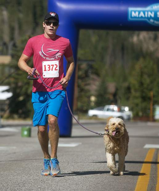 Brian Hilton, and his dog, Kahlua, cross the finish line for first place in the LAPS K94K run and walk fundraiser Saturday, Aug. 4, on Frisco's Main Street.