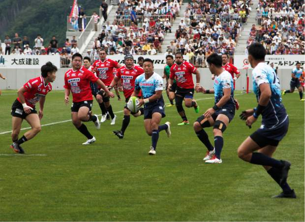 In this Aug. 19 photo, Yamaha Jubilo's Kira Tomokazu carries the ball during a memorial rugby match against Kamaishi Seawaves at Kamaishi Recovery Memorial Stadium in Kamaishi, northern Japan. Japan opened the new stadium Sunday for the 2019 Rugby World Cup on the site of a school that was destroyed by a devastating tsunami in 2011. The teams faced off in a memorial match in the small coastal city of Kamaishi to honor victims of the deadliest disaster in Japan's recent history.