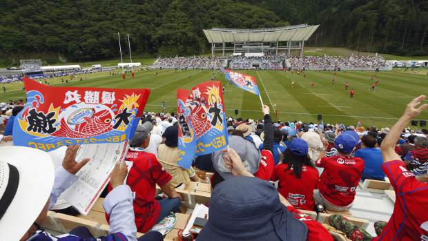 In this Sunday, Aug. 19, 2018, photo, fans watch as rugby players of Kamaishi Seawaves and Yamaha Jubilo play during an opening match at new Kamaishi Recovery Memorial Stadium in Kamaishi, northern Japan. Japan opened a new stadium for the 2019 Rugby World Cup on the site of a school that was destroyed by a devastating tsunami in 2011. About 6,500 fans turned out Sunday for a memorial match in the small coastal city of Kamaishi to honor the victims of the tsunami. (Yusuke Ogata/Kyodo News via AP)