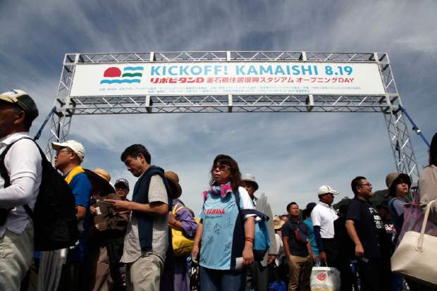 In this Sunday Aug. 19, 2018, photo, rugby funs queue up to enter Kamaishi Recovery Memorial Stadium to watch a memorial rugby match between the Kamaishi Seawaves and Yamaha Jubilo in Kamaishi, northern Japan. Japan opened the new stadium Sunday for the 2019 Rugby World Cup on the site of a school that was destroyed by a devastating tsunami in 2011. The stadium will host two matches in next year's World Cup, which will be played at 12 venues around Japan. (AP Photo/Koji Ueda)