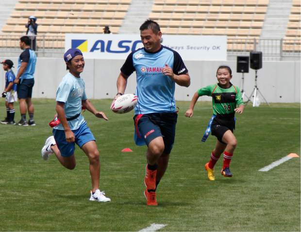 In this Sunday Aug. 19, 2018, photo, Yamaha Jubilo's Ayumu Goromaru, center, plays tag rugby with children before a memorial match between Yamaha and the Kamaishi Seawaves at Kamaishi Recovery Memorial Stadium in Kamaishi, northern Japan. Japan opened the new stadium Sunday for the 2019 Rugby World Cup on the site of a school that was destroyed by a devastating tsunami in 2011.
