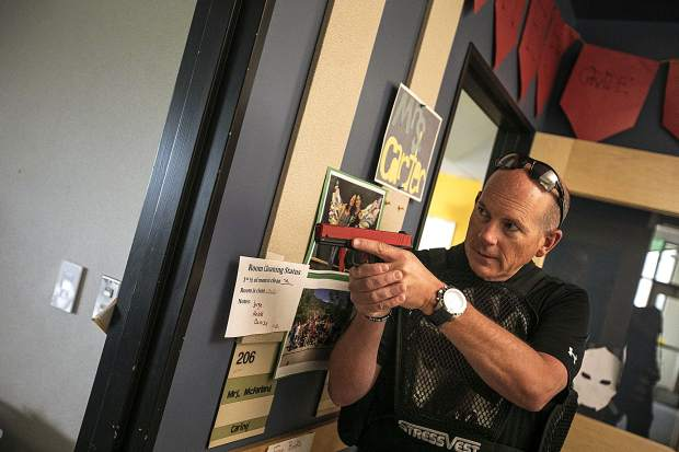 During a reality-based training, Summit County Sheriff lieutenant Thomas Whelan, left, points the laser tag gun at a school shooter in a hostage situation inside a classroom of Silverthorne Elementary School Wednesday, Aug. 1, in Silverthorne.