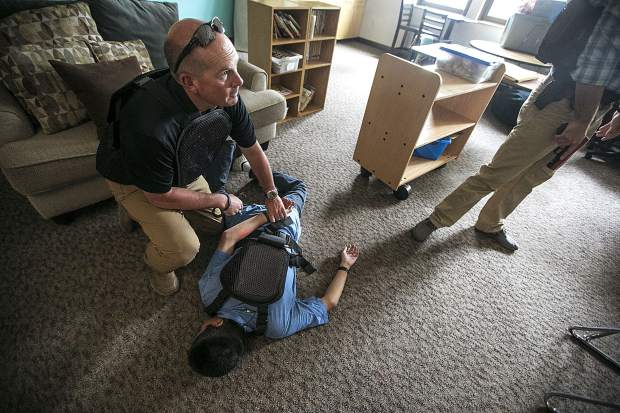 During a reality-based training, Summit County Sheriff lieutenant Thomas Whelan, left, handcuffs a school shooter, portrayed by Donovan Rubio, inside a classroom of Silverthorne Elementary School Wednesday, Aug. 1, in Silverthorne.