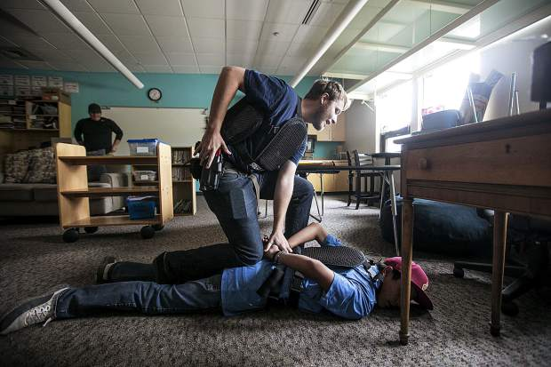 During a reality-based training, Summit Daily News reporter Sawyer D'Argonne participates in a scenario in arresting a school shooter, portrayed by Donovan Rubio, inside a classroom of Silverthorne Elementary School Wednesday, Aug. 1, in Silverthorne.