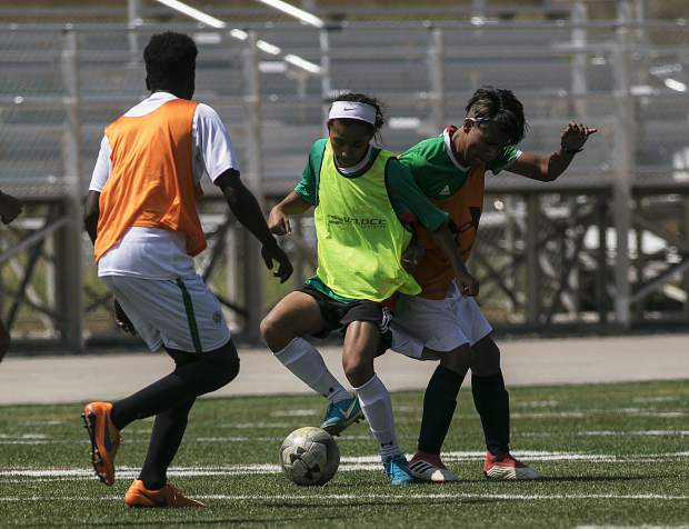 Summit High School senior striker Farid Infante (center) spins while possessing the ball versus a couple of teammates during varsity soccer practice on Monday, Aug. 20, at Climax Molybdenum Field at Tiger Stadium in Breckenridge.