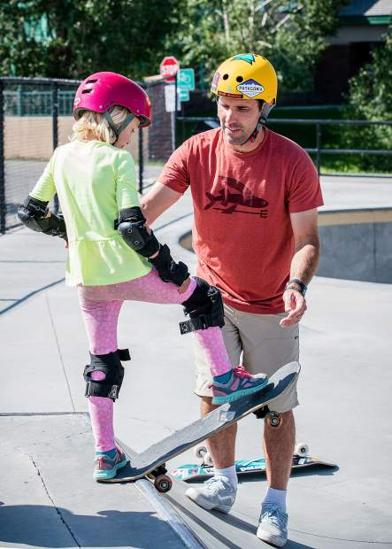 Any MacDonald, skateboarding legend and holder of 23 X-Games medals, helps Ophelia Burns, age 6 drop into the quarter pipe at the Breckenridge Skate Park.