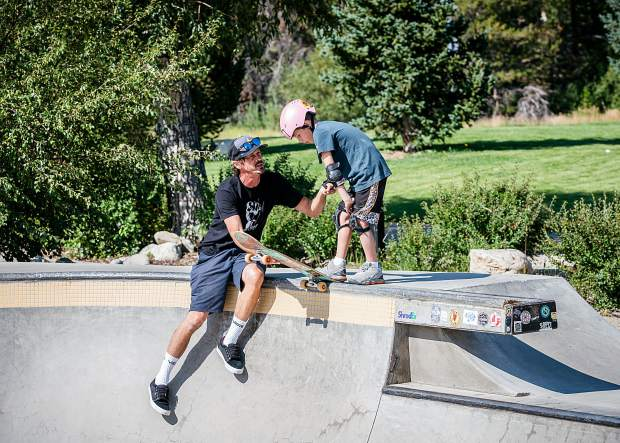 Bucky Lasek, the most decorated skater in vert X-Games history, helps Matt Muhlrad, a participant in the Breckenridge Recreation Center skateboard camp, learn to drop into the bowl.