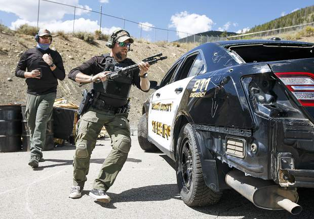 Dillon Police Department Sergeant Adam Nance hustles around the discarded vehicle in a tactical course of the Top Gun Competition among Summit County's law enforcement agencies Wednesday, Aug. 29, at the private shooting range in Dillon.
